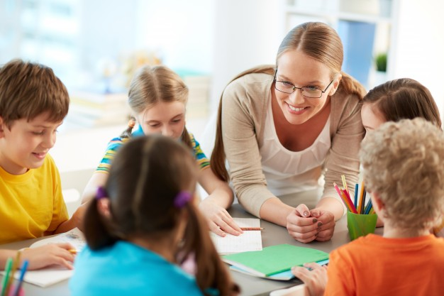 happy-teacher-listening-her-students_1098-2801